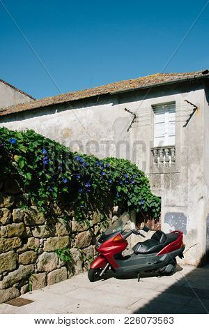 Small red motorbike parked on the street in sunny summer day, Bayona, Spain