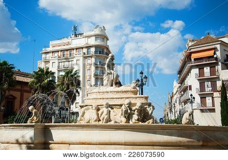 Water fountain on city square in sunny summer day, Sevilla, Spain