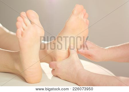 Experienced Hands Give A Foot Massage To A Young Womans Foot