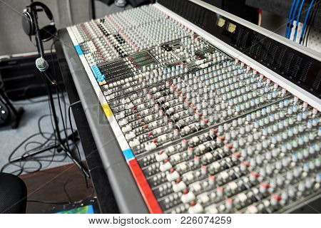 Mixing Desk Used For Combining Sounds Of Many Different Audio Signals And Microphone On Stand With H
