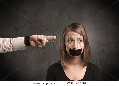 Caucasian business hand pointing at female employee with grunge background