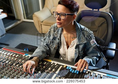 Thoughtful Modern Female Audio Engineer Concentrated On Mixing Sounds While Moving Faders And Twisti