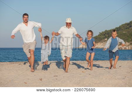 Happy Family Group Of Five, Three Generations Are Running Along The Beach.