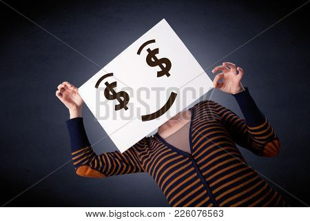 Young casual woman hiding behind a greedy face drawing on cardboard