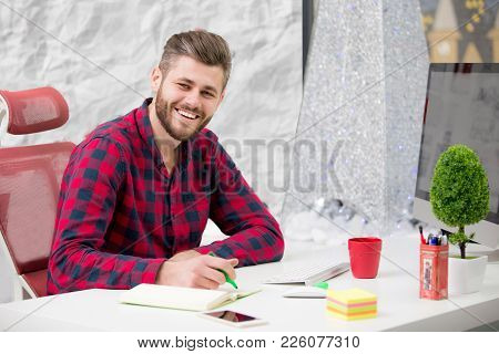 Concentrated On Work. Concentrated Young Beard Man Working On Laptop While Sitting At His Working Pl