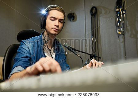 Thoughtful Concentrated Hipster Sound Engineer With Tattoo On Neck Listening To Song And Changing So