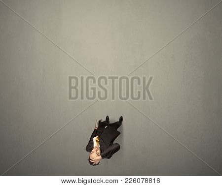 Young businessman contemplating a decision standing on a grey surface