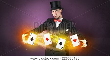 Illusionist in tails bandy play cards between his two hands
