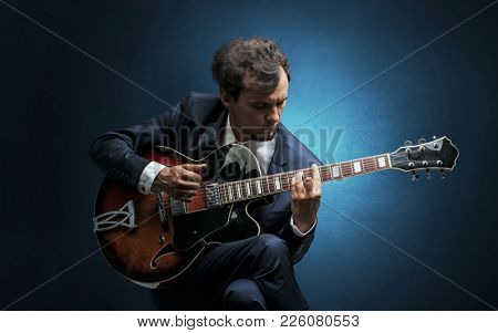 Lonely guitarist composing on cello with nothing around