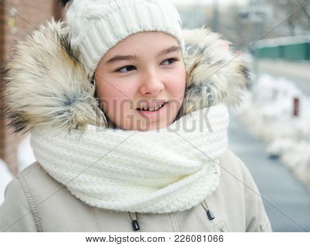 Happy teenage girl in warm jacket, knitted hat and scarf. Winter street photography.