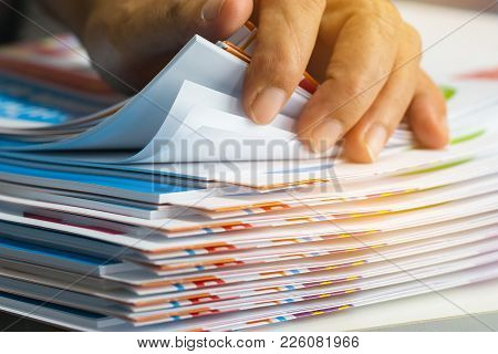 Businessman Hands Searching Unfinished Documents Stacks Of Paper Files On Office Desk For Report Pap