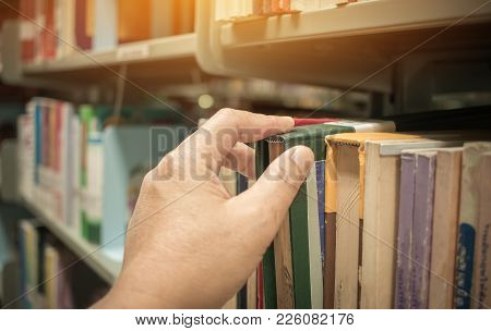 Student Man Hand Taking Book From The Shelf Over Blur Library Book Shelf Natural Background, Bokeh O
