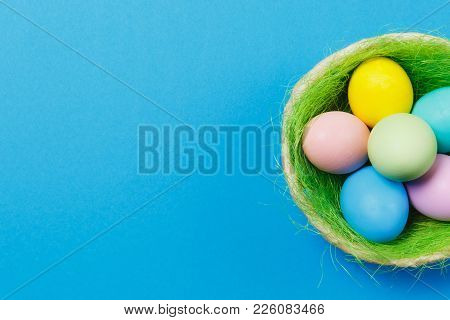 Six Colorful Pastel Monophonic Painted Easter Eggs In Basket With Green Grass Isolated On Blue Backg