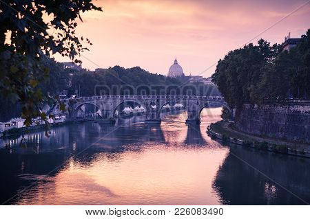 Rome Cityscape With Old Bridge Over Tiber River In Evening