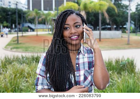 Beautiful African Woman With Dreadlocks At Mobile Phone Outdoors In The Summer