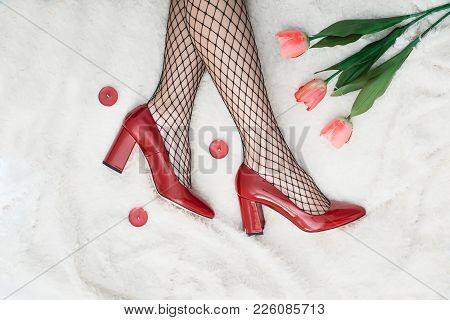 Sexy Female Legs In High Heel Red Shoes And Fishnet Stockings. Retro Style