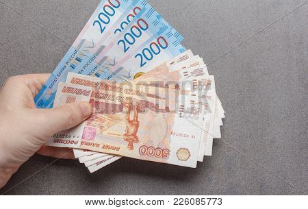 New Russian Banknotes Denominated In 2000 And 5000 Rubles In Male Hands Close-up On A Gray Backgroun