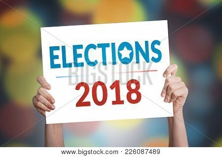 Elections 2018 Card In Hand With Bokeh Background