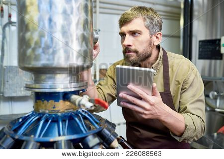 Thoughtful Concentrated Male Technician In Apron Repairing Brewery Machine Using Maintenance Instruc