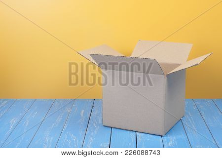 Postage And Packing Service - Open Package On A Blue Wood And Yellow Wall Background.