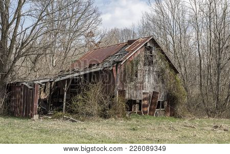 A Decaying Wooden Barn With A Rusting Roof In A Rural Area.