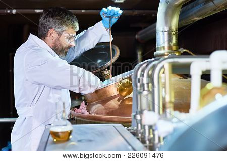 Serious Concentrated Handsome Middle-aged Brewer Wearing Protective Eyewear And Gloves Examining Fer