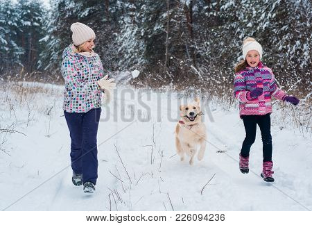 mother and daughter running with white retriever dog in winter park. Cute young family fun in winter park with their dog golden retriever on a sunny day and smiling. Friendship, pet and human.