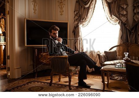 Elegant Prosperous Businessman In Formal Black Suit, Sits On Chair In Royal Room, Feels Relaxed, Has