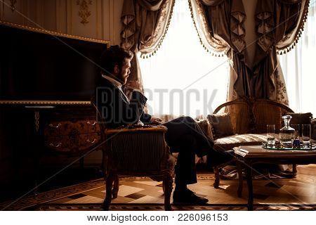 Indoor Shot Of Thoughtful Gorgeous Businessman Or Enterpreneur Wears Black Suit, Sits In Cozy Room W