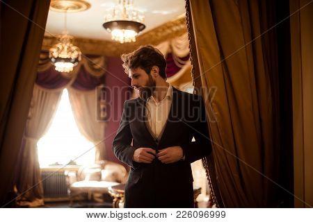 Horizontal Shot Of Bearded Male Eneterpreneur Dressed In Formal Suit, Stands In Royal Room With Luxu