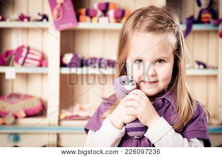 cute little girl standing in front of a shelf filled with cuddly toys poster