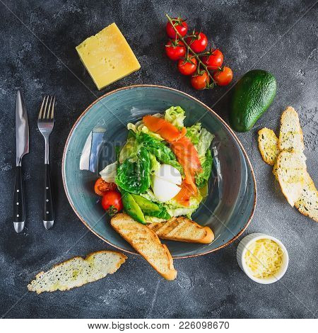 Caesar Salad With Egg, Salmon, Avocado, Cherry Tomatoes And Grilled Toast On Grey Background. Flat L