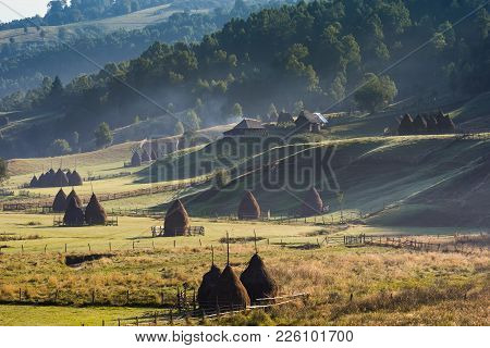Beautiful rural mountain landscape in the morning light with fog, old houses and haystacks, Fundatur