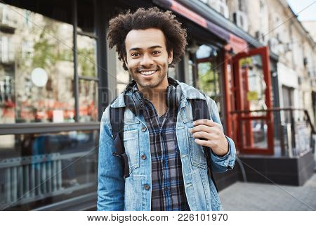 Handsome Stylish African-american With Afro Hairstyle Wearing Denim Coat And Headphones Walking The