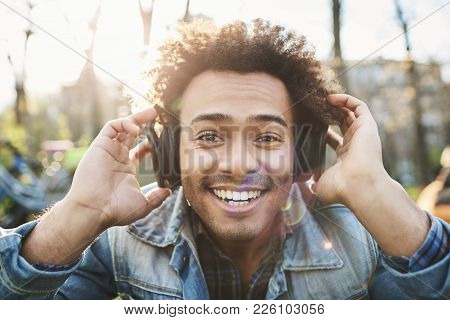 Portrait Of Positive Adult Dark-skinned Man Smiling Broadly While Sitting In Park, Listening To Musi