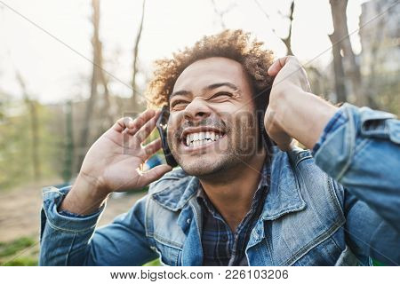 Side-view Outdoor Portrait Of Excited Happy African Man With Afro Hairstyle Holding Headphones While