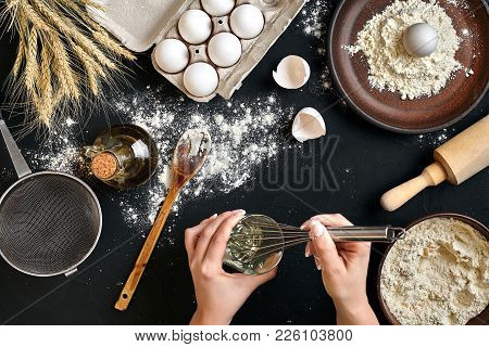 Whipping Eggs. Chef Hands Close-up Whisk Eggs On A Black Background. View From Above. Still Life. Fl