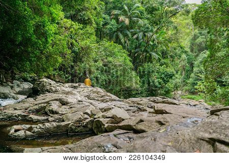 A Girl Wearing A Yellow Blanket Sits And Reflects Peacefully On A Rocky Outcrop In The Gold Coast Ra