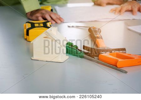 Wooden House Model And Tools On Conference Table With Technician, Engineer Planning Start Up New Pro