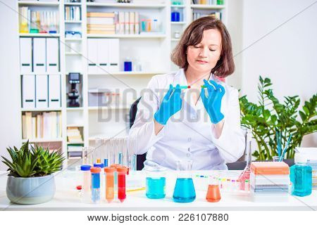 Female Scientist Injects Reagent Into The Plant In A Laboratory. Researcher Researching In The Labor