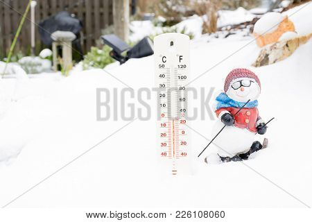 Thermometer In Winter Garden With Small Cute Doll Skiing