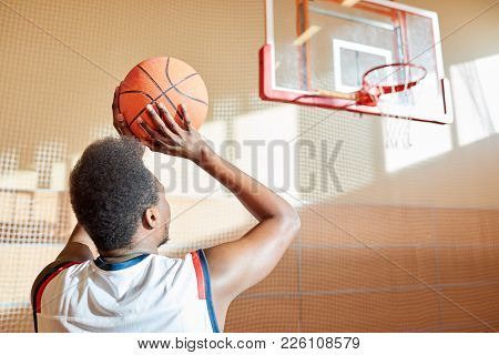 Rear View Of Ambitious African-american Sportsman Preparing For Score Aiming Before Throwing Ball In