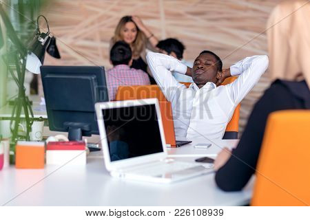 Cheerful Black Guy Is Watching At His Laptop Screen, At His Work Place, With Arms Behind The Head, R