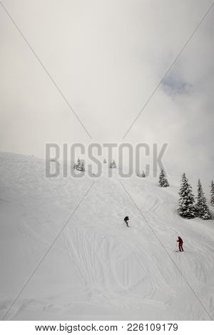 Two Skiers On A Ski Run With Clouds