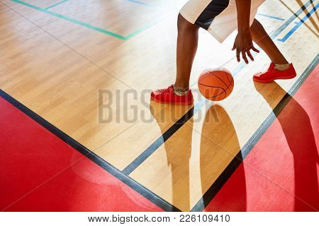 Close-up Of Unrecognizable African Basketball Player Moving With Ball While Dribbling Between Legs O