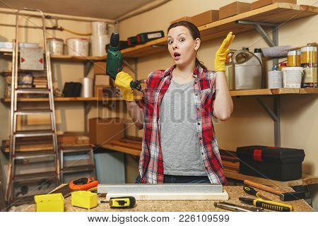 Beautiful Caucasian Young Brown-hair Woman In Plaid Shirt And Gray T-shirt Working In Carpentry Work