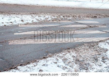 Winter In The City Zebra Pedestrian Crossing. Dirty Snow Tracks Auto Car Wheels, Foot Prints Of Pede