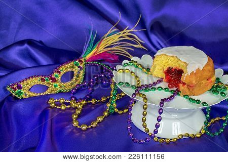 Fat Tuesday Paczki With Mardi Gras Party Beads On White Pedestal Plate With Sequin Mask On Purple Sa
