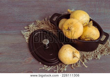 Yellow Turnip In A Cast-iron Pot On A Burlap Napkin On An Old Wooden Table. Lenten Dishes. Toned Pho