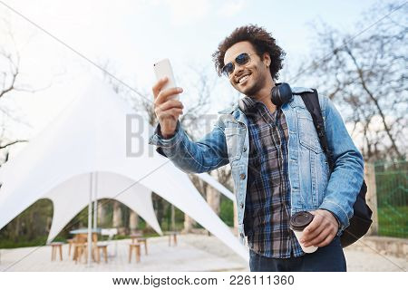 Outdoor Portarit Of Happy Sincere African American Man In Stylish Glasses And Denim Coat, Holding Cu